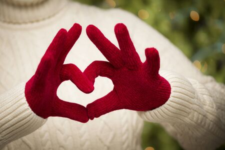 Woman in Sweater with Seasonal Red Mittens Holding Out a Heart Sign with Her Hands. Stock Photo - 16580275