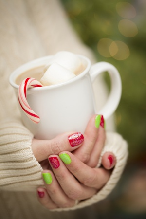 Woman in Sweater with Seasonal Red and Green Nail Polish Holding a Warm Cup of Hot Cocoa. photo