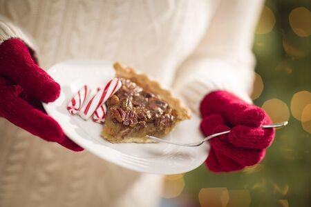 pecan pie: La mujer llevaba un suéter y estacionales manoplas rojas con un plato de Pecan Pie con caramelos de menta.