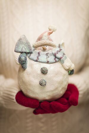 Woman Wearing A Sweater and Seasonal Red Mittens Holding An Ornate Glass Snowman. Stock Photo - 16580293