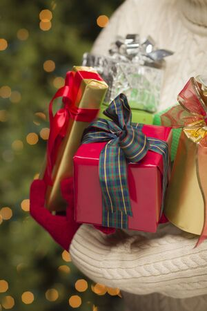 beautifully wrapped: Woman Wearing A Sweater and Seasonal Red Mittens Against an Abstract Green and Golden Background Holding Beautifully Wrapped Christmas Gifts.