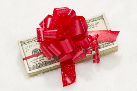 christmas profits: Stack of One Hundred Dollar Bills with Red Ribbon on Snow Flakes.