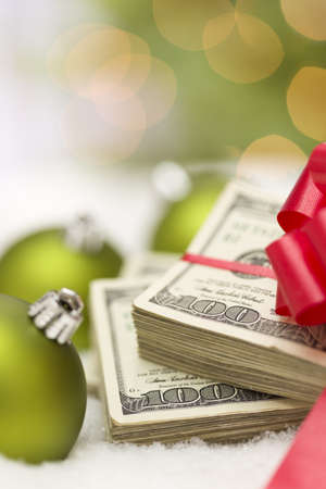 christmas profits: Stack of One Hundred Dollar Bills with Red Bow Near Green Christmas Ornaments on Snow Flakes.