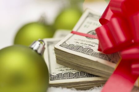 holiday profits: Stack of One Hundred Dollar Bills with Red Bow Near Green Christmas Ornaments on Snow Flakes.