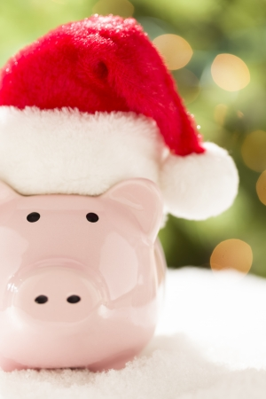 Pink Piggy Bank Wearing Red and White Santa Hat on Snowflakes with Abstract Green and Golden Background. photo