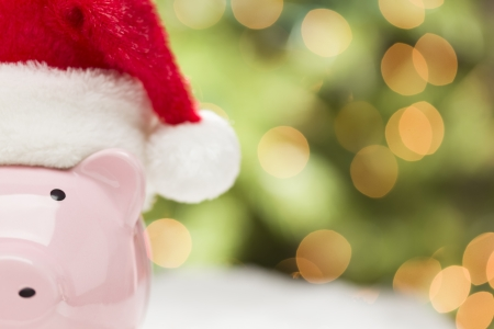 christmas debt: Pink Piggy Bank Wearing Red and White Santa Hat on Snowflakes with Abstract Green and Golden Background - Room for Your Own Text. Stock Photo