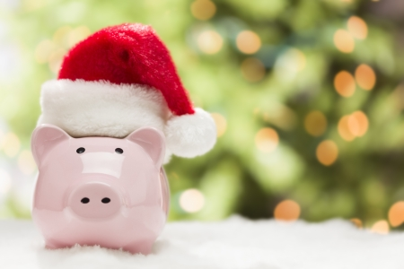 Pink Piggy Bank Wearing Red and White Santa Hat on Snowflakes with Abstract Green and Golden Background - Room for Your Own Text. Banco de Imagens - 16580150