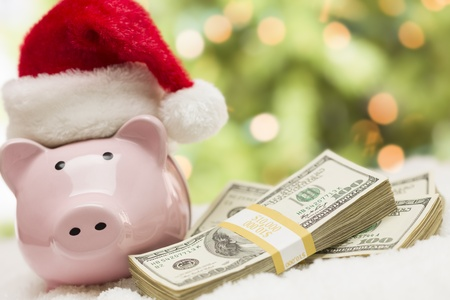 christmas savings: Pink Piggy Bank Wearing Santa Hat Near Stacks of Hundreds of Dollars of Money on Snowflakes. Stock Photo