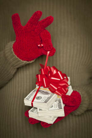 Woman Wearing Red Mittens and Green Sweater Holding Stacks of Hundreds of Dollars of Money with Red Ribbon. photo