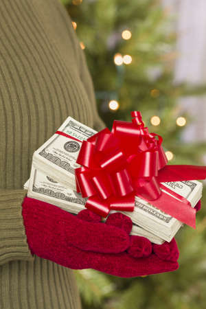 gifting: Woman Wearing Red Mittens and Green Sweater Holding Stacks of Hundreds of Dollars of Money with Red Ribbon. Stock Photo