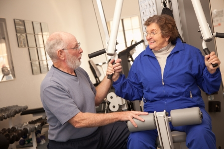 70s adult: Active Senior Adult Couple Working Out Together in the Gym.