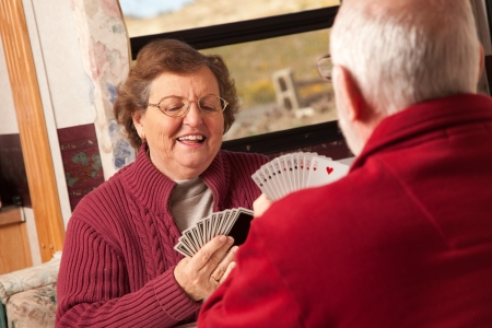 rv: Happy Senior Adult Couple Playing Cards in Thier Travel Trailer RV.