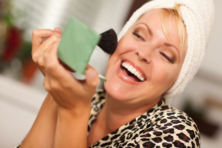 one mid adult woman only: Attractive Blonde Woman Applying Her Makeup Indoors.