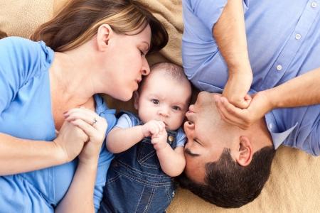 Mixed Race Family with Baby Playing Face Up on the Blanket Stock Photo - 16717169