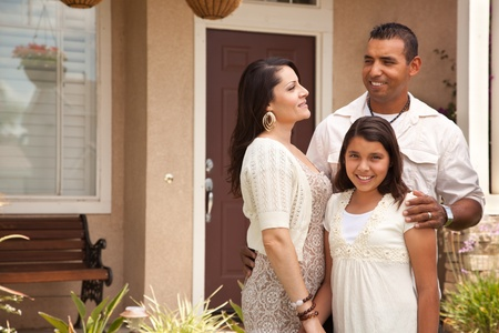 Happy Hispanic Mother, Father and Daughter in Front of Their Home. photo