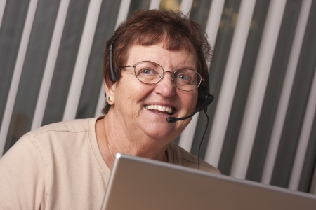 Smiling Senior Adult Woman with Telephone Headset In Front of Computer Monitor. photo