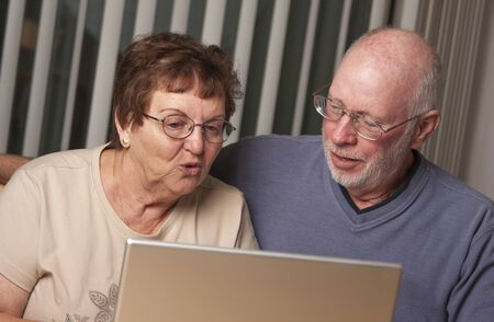 Smiling Senior Adult Couple Having Fun on the Computer Laptop Together. photo