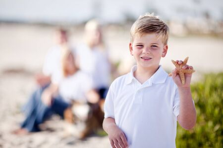 starfish beach: Cute Little Blonde Boy Showing Off His Starfish at the Beach.
