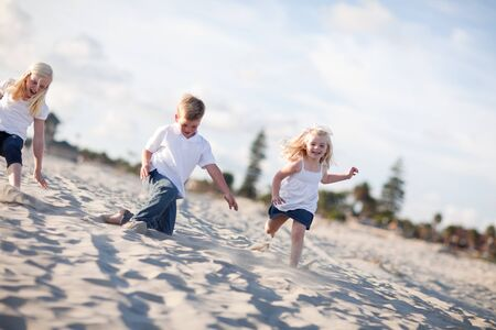 Adorable Brother and Sisters Having Fun at the Beach one Afternoon. photo