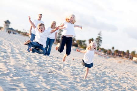 Happy Sibling Children Jumping for Joy at the Beach as Parents Watch. photo