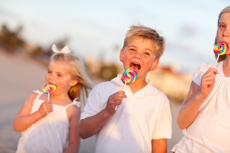 Cute Brother and Sisters Enjoying Their Lollipops Outside at the Beach. Banco de Imagens