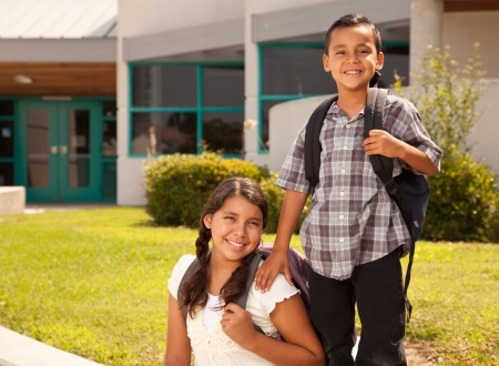 campus building: Cute Hispanic Brother and Sister Wearing Backpacks Ready for School.