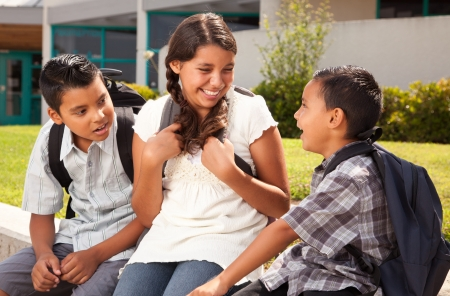 Cute Hispanic Brothers and Sister Talking Ready for School on Morning. photo