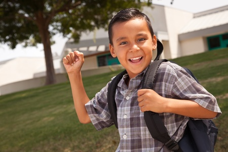 Happy Young Hispanic Boy with First in the Air Wearing Backpack Ready for School. photo