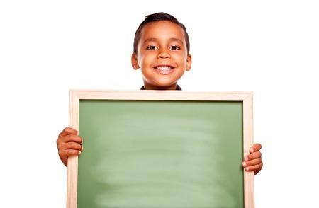 niños latinos: Muchacho hispánico lindo que sostiene la pizarra en blanco listo para su propio mensaje aislado en un fondo blanco.
