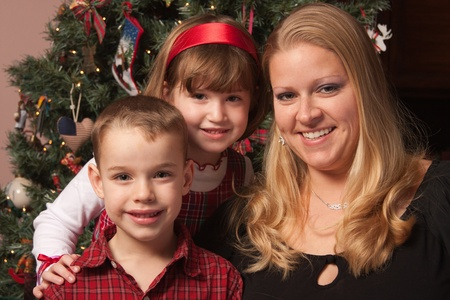 Cute Children and Mother Posing for a Portrait in Front Of Holiday Tree. photo