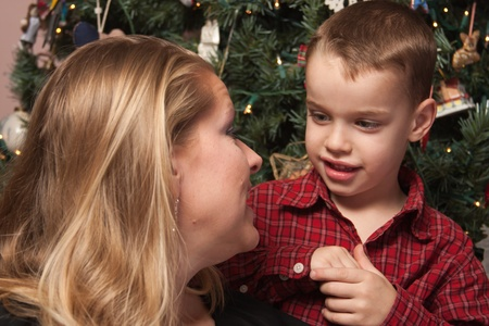 Adorable Son Talking to Mom in Front Of Their Christmas Tree. photo