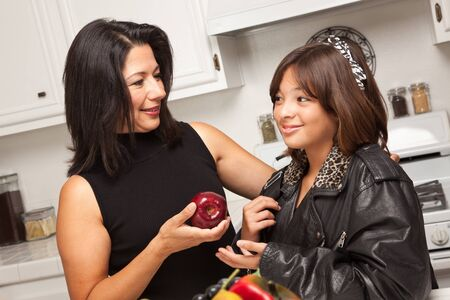 Pretty Hispanic Girl and Mother Getting Ready for School in the Kitchen. photo