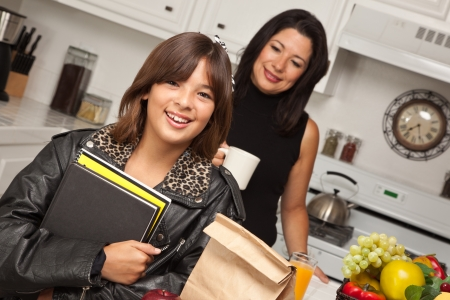 latin mother: Pretty Hispanic Girl and Mother Getting Ready for School in the Kitchen.