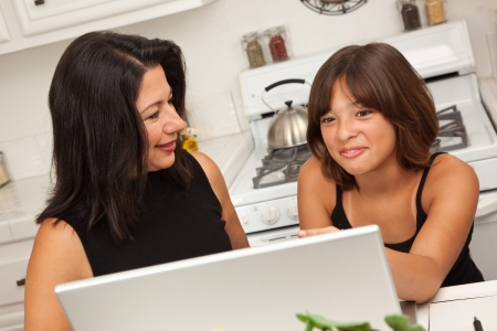 Attractive Hispanic Mother and Mixed Race Daughter in the Kitchen using the Laptop Computer Together. photo