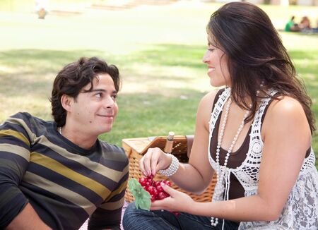 Attractive Hispanic Couple Having a Picnic Outdoors in the Park. photo