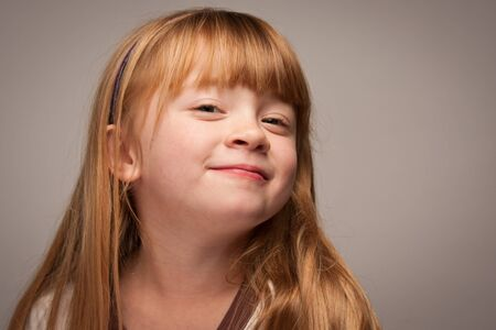Fun Portrait of an Adorable Red Haired Girl on a Grey Background. photo