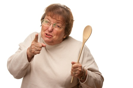70s adult: Upset Senior Woman with The Wooden Spoon Isolated on a White Background.