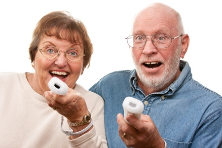 wii: Happy Senior Couple Play Video Game with Remote Controls On a White Background. Stock Photo