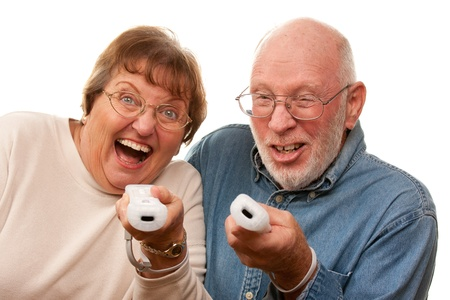 aging: Happy Senior Couple Play Video Game with Remote Controls On a White Background. Stock Photo