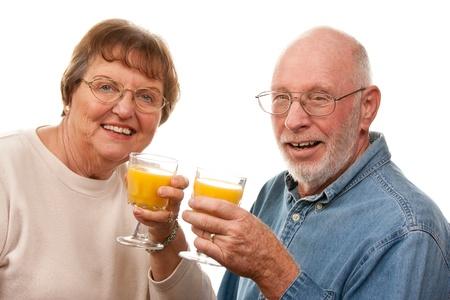 Happy Senior Couple with Glasses of Orange Juice Isolated on a White Background. Stock Photo - 16717235