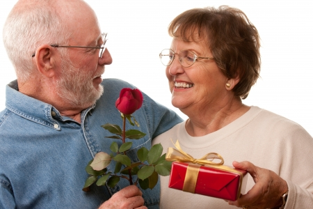 Happy Senior Couple with Gift and Red Rose Isolated on a White Background. photo