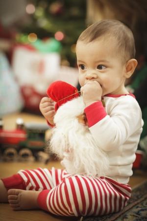 baby near christmas tree: Cute Infant Baby Enjoying Christmas Morning Near The Tree. Stock Photo