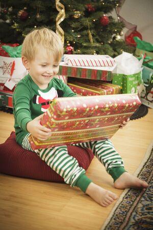 Cute Young Boy Enjoying Christmas Morning Near The Tree. Stock Photo - 16825712