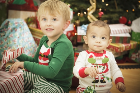 baby near christmas tree: Cute Infant Baby and Young Boy Enjoying Christmas Morning Near The Tree.