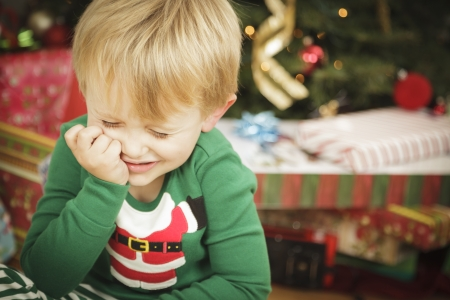 holding a christmas ornament: Grumpy Cute Young Boy on Christmas Morning Near The Tree. Stock Photo