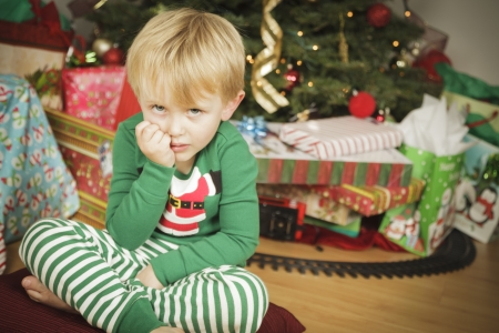 christmas morning: Grumpy Cute Young Boy on Christmas Morning Near The Tree. Stock Photo