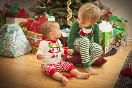 Cute Infant Baby and Young Boy Enjoying Christmas Morning Near The Tree. Stock Photo - 16825705