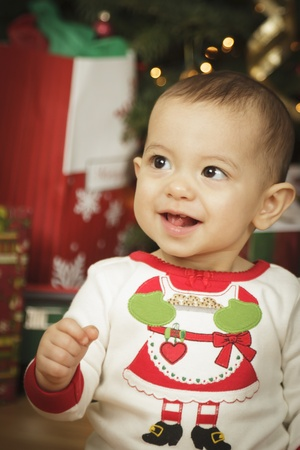 Cute Infant Baby Enjoying Christmas Morning Near The Tree. photo