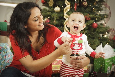 xmas baby: Young Attractive Ethnic Woman With Her Newborn Baby Near The Christmas Tree. Stock Photo