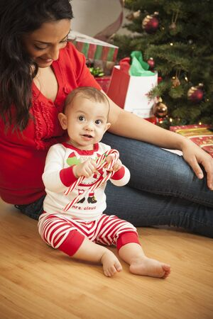 baby near christmas tree: Young Attractive Ethnic Woman With Her Newborn Baby Near The Christmas Tree. Stock Photo
